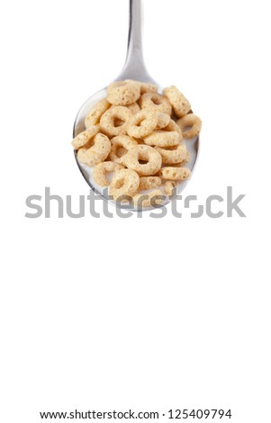 Close-up shot of a spoon with cereal rings and milk against white background. - stock photo