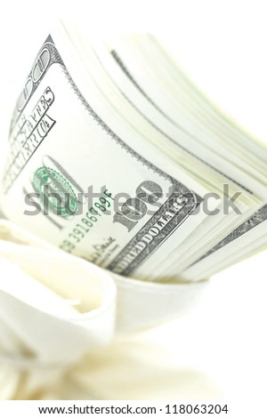 close up shot of a stack of american dollar bills plugged in the opening of a white bag