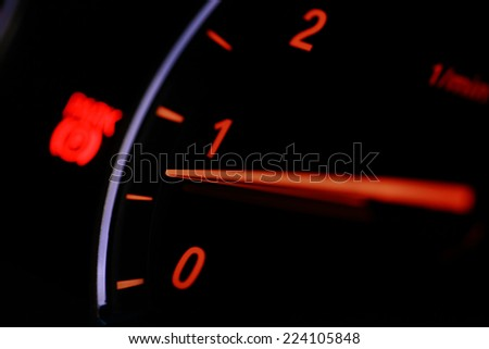 Close up shot of a tachometer in a car, at night.