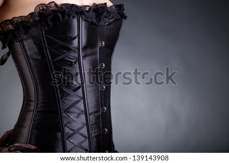 Close-up shot of a woman in black corset, with copy-space for your text - stock photo