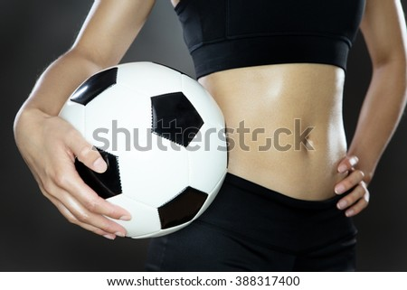 close up shot of a woman's midriff holding a football shot in the studio on a gray background - stock photo
