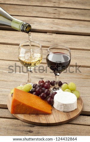 Close-up shot of a wooden board with cheese and grapes while white wine being poured from wine bottle. - stock photo