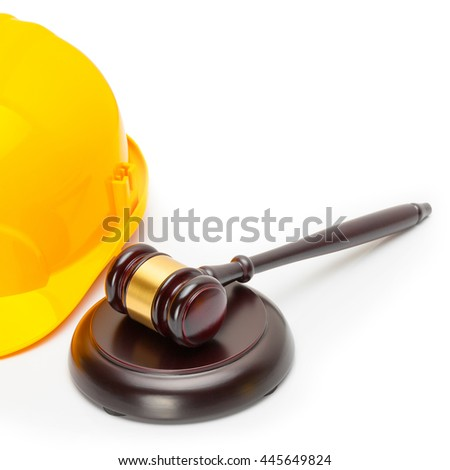 Close up shot of a wooden judge gavel near yellow protective helmet - stock photo
