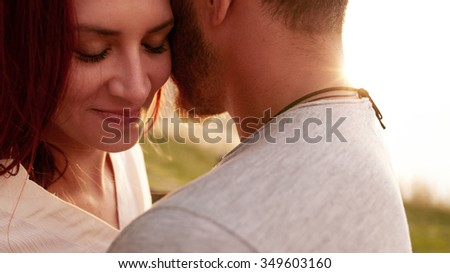 Close up shot of affectionate young woman embracing her boyfriend with her eyes closed. Romantic young couple together outdoors on a summer day. - stock photo