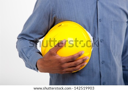 Close up shot of African man holding a yellow hard hat on an isolated background