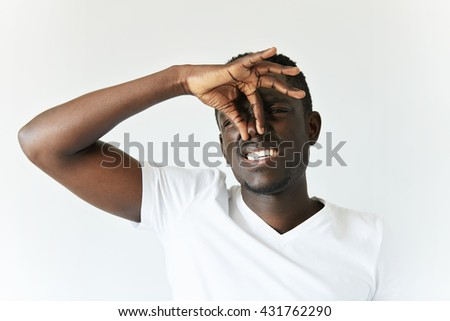Close up shot of African man in casual clothes pinching his nose to avoid bad smell. Dark-skinned student looking at the camera with disgusted expression while something is stinking. Body language - stock photo