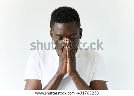 Close up shot of African man wearing white T-shirt standing with depressed and sad look, covering his face, thinking of something bad happened, hoping for the best. Human face expressions and emotions - stock photo