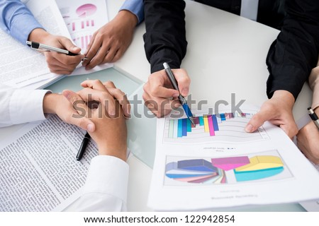 Close-up shot of an analytical team working with the latest financial results - stock photo