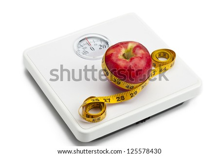 Close-up shot of an apple tied with measuring tape on weight scale. - stock photo