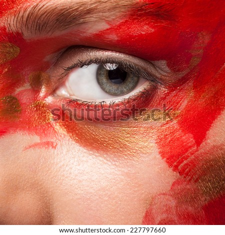 Close up shot of an eye with painted face. Red and gold tones. Perfect clean skin. Stage make up. Vivid colors