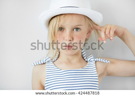 Close up shot of  annoyed and angry girl wearing white hat and striped dress, holding index finger at her head with 'are you crazy' gesture. Isolated portrait of little Caucasian 5-year old child  - stock photo