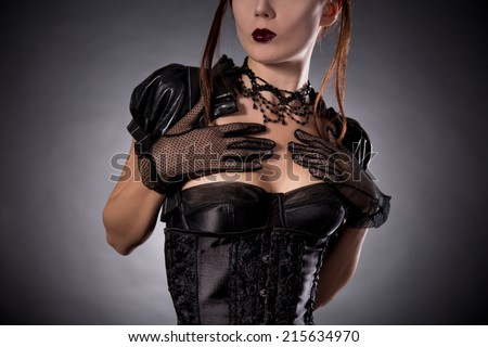 Close-up shot of attractive young woman in Victorian style corset and jewelry, studio shot  - stock photo