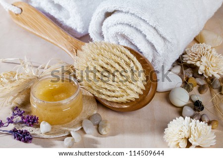 Close-up shot of bathing brush with spa cream and spa stones. - stock photo