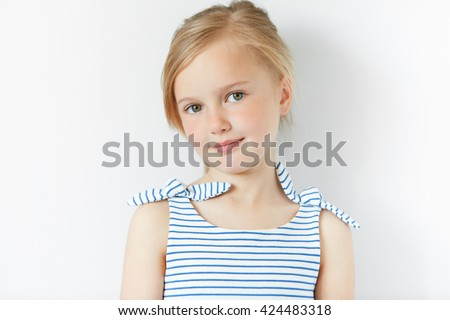 Close up shot of beautiful blonde Caucasian little girl wearing striped dress, looking at the camera with adorable smile, posing against white copy space concrete wall. Happy childhood concept - stock photo