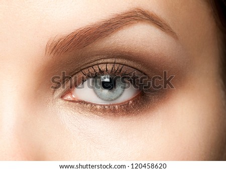 Close-up shot of beautiful female blue eye with bright fashion makeup - stock photo