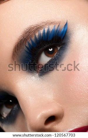Close-up shot of beautiful female eye with bright fashion makeup. Woman eye with blue false eyelashes