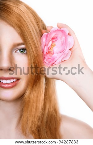 Close-up shot of beautiful happy smiling girl with pink flower