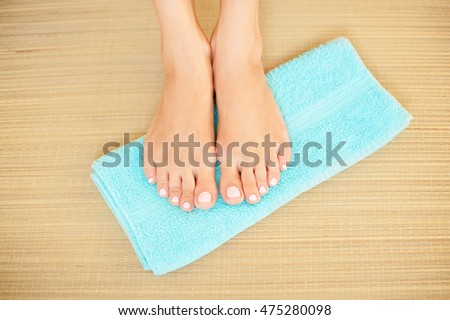 Close-up shot of beautiful woman feet with bright pink nails on blue towel