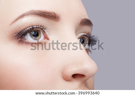 Close-up shot of beautiful young woman eye zone with day  make up  - stock photo