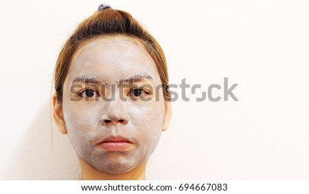 Close up shot of beauty asian young woman using a black face mask on wall white background