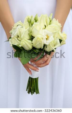 Close up shot of bride hands holding beautiful wedding bouquet with green roses - stock photo