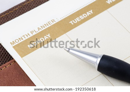 close up shot of brown planner book with pen - stock photo