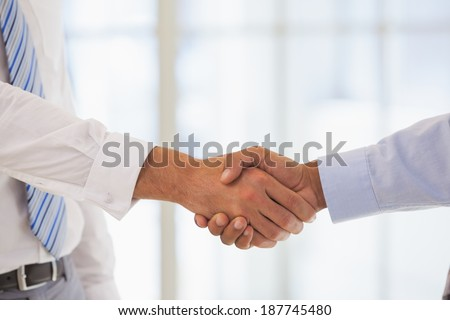 Close-up shot of businessmen shaking hands in the office