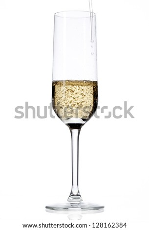 Close-up shot of champagne flute being filled over plain white background.