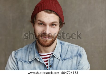Close up shot of charismatic fashionable young European male with thick beard wearing trendy hat and denim jacket, staring at camera and smiling with happy cheerful look, enjoying free time at cafe