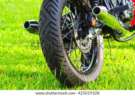 Close-up shot of classical motocycle  tire tread on a green lawn - stock photo
