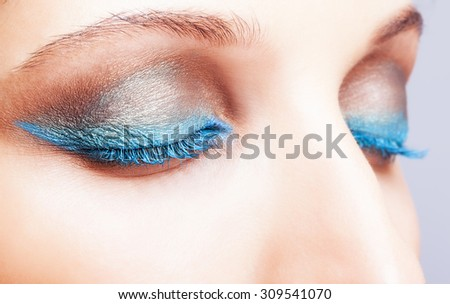 Close-up shot of closed female eyes blue color make-up - stock photo