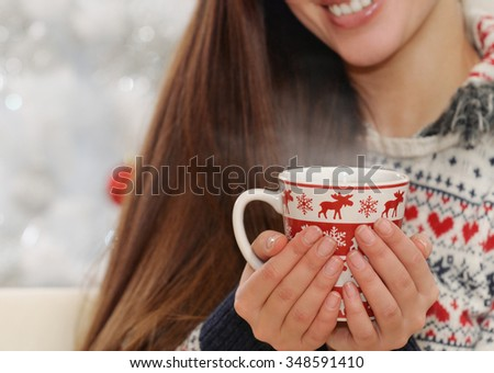 close up shot of cup in woman's hands with hot drink on Christmas tree background, happy holiday concept