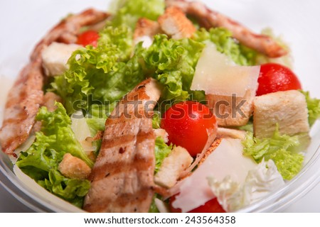 Close-up shot of delicious Caesar salad with grilled chicken meat  - stock photo