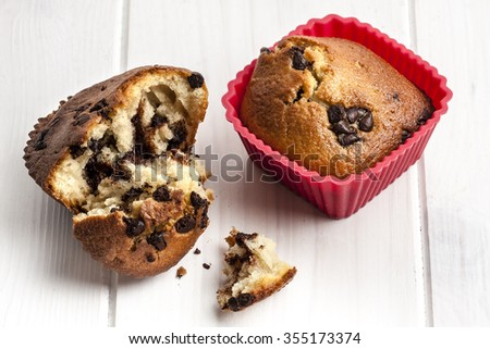 Close up shot of delicious chocolate muffin on red silicone cupcake case next to open muffin and crumbs on white wooden table - stock photo