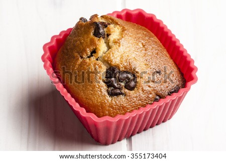 Close up shot of delicious chocolate muffin on red silicone cupcake case on white wooden table