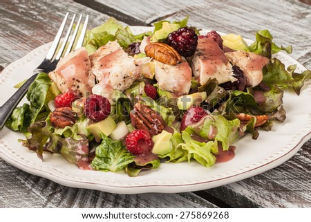 Close-up shot of freshly harvested lettuce, grilled chicken, avocado, raspberry, pecan salad - stock photo