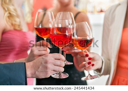 Close up Shot of Friends Tossing Glasses of Red Wine in a Party. - stock photo