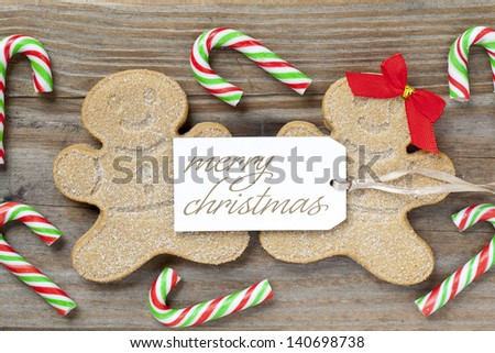 Close-up shot of gingerbread couple with a Merry Christmas tag and candy cane over wooden plank.