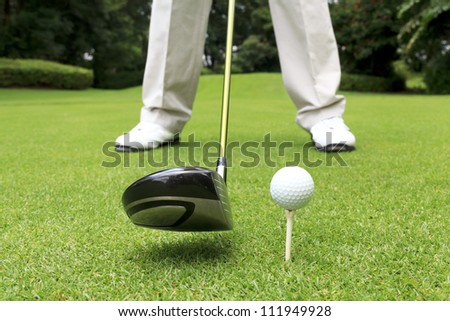 close up shot of golfer ready to tee off - stock photo