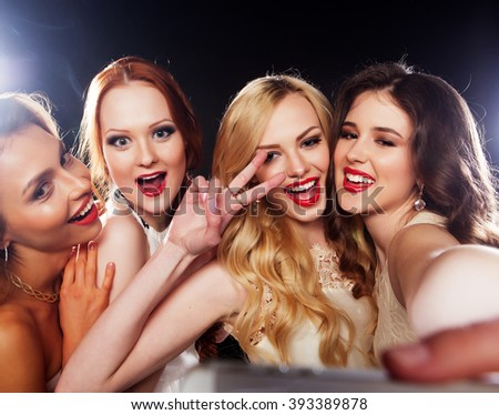 Close-up shot of group of laughing girls having party, take selfie with smartphone - stock photo