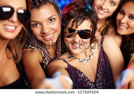 Close-up shot of group of partying girls looking at camera