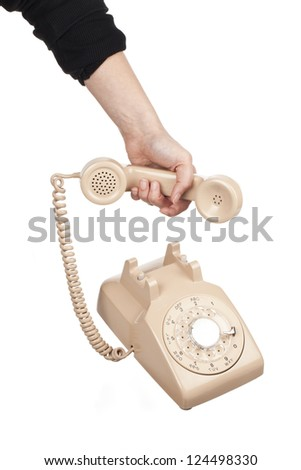 Close-up shot of hand holding receiver of rotary dial phone over white background - stock photo