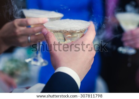 Close up Shot of Hands Tossing Glasses of Alcohol at a Party or event, with decorated catering bouquet table on open air event,