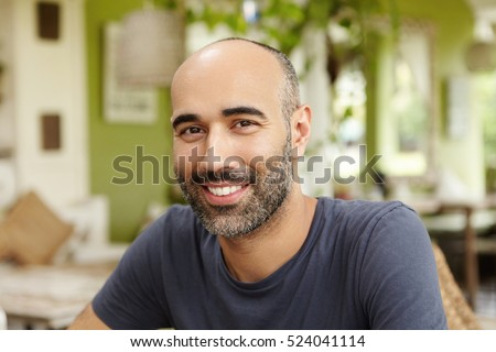Close up shot of handsome Caucasian man with beard dressed in t-shirt looking and smiling at camera with happy cheerful expression, sitting at sidewalk restaurant on sunny day, waiting for friends