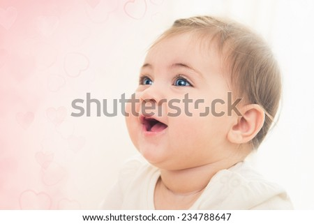 Close up shot of happy smiling baby girl with blue eyes. Soft focus.