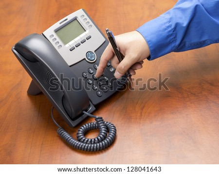 Close-up shot of human hand dialing number on black land line phone on wooden desk.