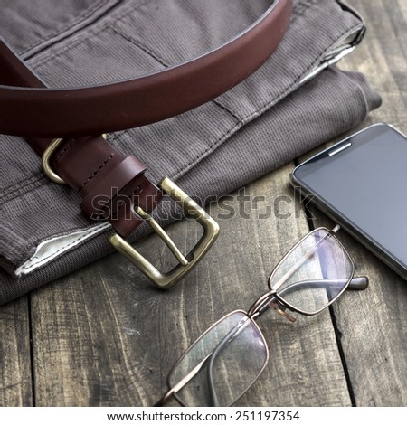 Close up  shot of men's winter clothes laid out on a wooden background - stock photo