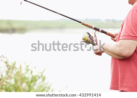 Close-up shot of middle aged man hand holding rod and spinning reel on summer lake - fishing concept - stock photo