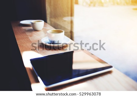 Close up shot of modern touch pad with mock up screen, gadget for multimedia files and data information from web site and wireless internet connection. Digital tablet and cup of coffee in interior