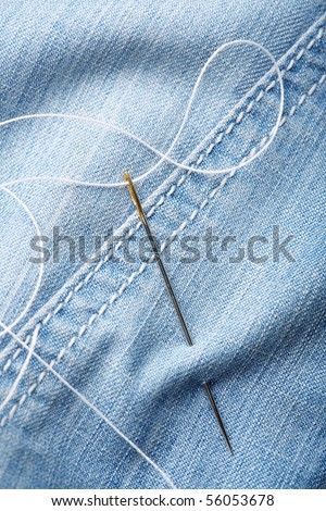 Close-up shot of needle with thread on jeans material. Close-up. - stock photo